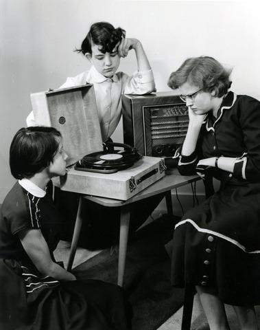 602671 - Jaren '50. Luisterplezier. Platenspeler. Geënsceneerde foto; meisjes zitten naast een platenspeler te luisteren.
