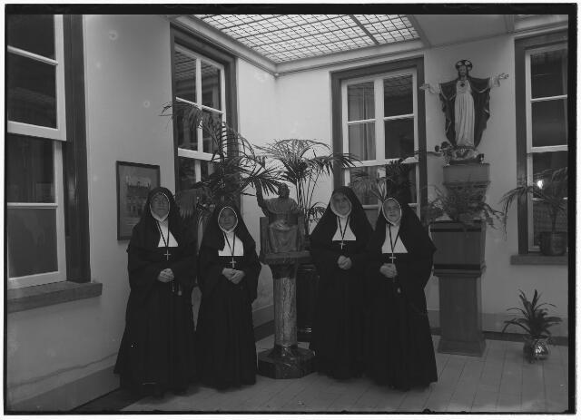 050961 - Van links naar rechts zuster Constantia Stouthamer, zuster Maria Magdalene Ali, zuster Marie Louise van Krijt en zuster Jozefinne Kerkers, leden van de congregatie van zusters van O.L.V. Moeder van Barmhartigheid (Oude Dijk). In het midden het beeld van de stichter van de congregatie, mgr. Zwijsen.