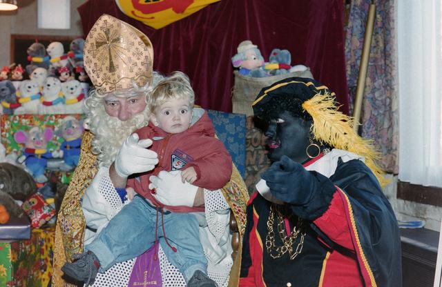 1237_001_003_014 - Feest. Korvel Winkelstraat. Sint Nicolaasviering. Een kind poseert met Sinterklaas en Zwarte Piet tijdens een Sinterklaasfeest georganiseerd door winkeliersvereniging Korvel Vooruit op 27 november 1999. Sint en Piet wijzen richting de camera in een poging om het kind in de lens te laten kijken.