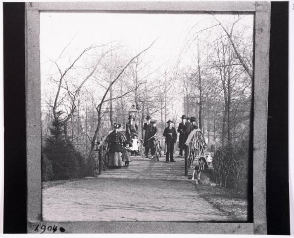 035109 - Houten brug in het Wilhelminapark met daarop een aantal heren met hoed en moeders met kinderen