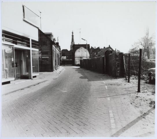 025524 - Langestraat na afbraak van wijnhandel Verbunt. Op de achtergrond de Heikese kerk (foto gemaakt in periode 1972-1980)
