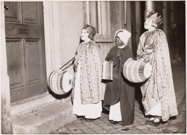 053094 - Driekoningen zingen.  op drie koningenavond gaan kinderen te Tilburg met verlichtte lampions of uitgeholde pronkappels langs de deuren onder het zingen van toepasselijke oude deuntjes. Foto: hier zo'n drietal waarbij drie kinderen een lampion dragen.