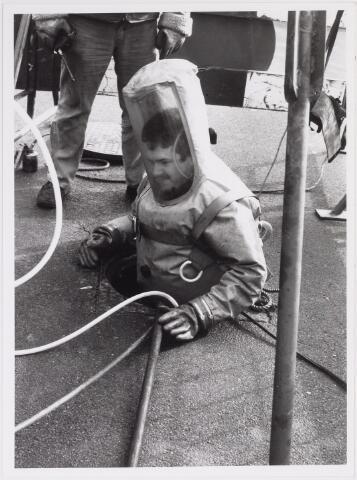 042246 - Riolering. Personeel van Van Hees bezig met het zuiveren en herstellen van de riolering in de Groenstraat ter hoogte van kinderwagenfabriek Mutsaerts. Een medewerker daalt af in het riool