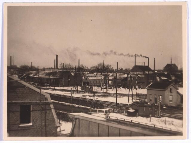022826 - Overweg bij de Bosscheweg omstreeks 1917. Rechts het huisje van de seinwachter. Links achter het spoor de vernisfabriek van Lommen en rechts daarvan, het hoge gebouw, de stoomketelmakerij van Hagoort, later kolenhandel Van Ierland.