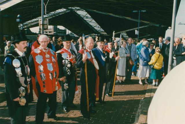 651305 - Tilburg, 125 jaar stad aan het spoor. Manifestatie. Geflankeert door de  koningen en hoofdlieden van de drie Tilburgse gilden St. Joris, St. Dionysius en St. Sebastiaan staat de loco-burgemeester van Tilburg, de heer van Eijkeren de treingasten op te wachten in het Tilburgse station. Het dak van  dat station, hier deels te zien, kreeg van de Tilburgse bevolking de bijnaam 'Kroepoekdak'.