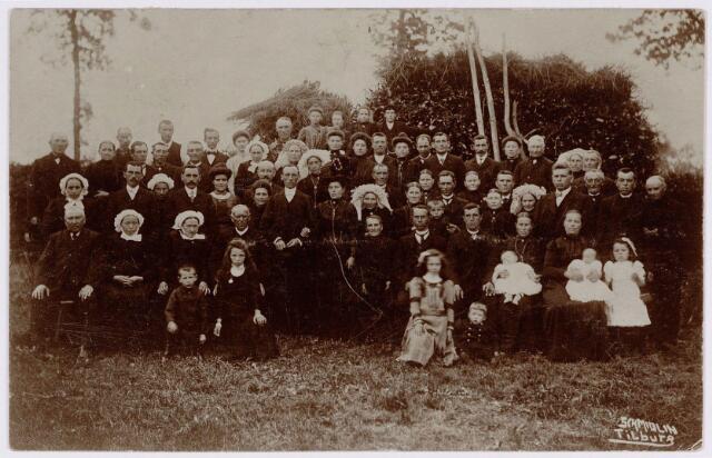 """650429 - Schmidlin. Deze (onbekende) familiegroep werd gefotografeerd ter gelegenheid van een huwelijk omstreeks 1910. Logistiek gezien was het niet handig om met een dergelijke groep naar de fotostudio te gaan, dus fotografeerde Louis Schmidlin op locatie.  Een aanvulling (na de publicatie van deze foto) leverde de identificatie van een gedeelte van de geportretteerden op. Het betreft de huwelijksdag van het echtpaar Zebregts-Maas op 31 mei 1911 te Tilburg.  Het bruidspaar staat in het midden van de foto opgesteld. Bruidegom is Michael Maria Zebregts, zijn bruid Wilhelmina Maas. Direct links naast de bruidegom vader Hendrikus Zebregs (Tilburg 1849-1933), weduwnaar van Maria Elisabeth Philipsen. Achter vader Zebregs zien we het echtpaar Zebregts-Matthijssen, resp. een broer en schoonzus van de bruidegom. Naast de bruidegom zien we nog (met snor) Cornelis van Meerendonk, een zwager.  De families Zebreg(t)s en Maas staan resp. links en rechts op de foto, aan de zijde van het familielid waaraan zij gerelateerd waren.  Binnen de familie Zebreg(t)s zijn verschillende schrijfwijzen bekend met betrekking tot de familienaam.   Deze foto onderscheid zich door de aanwezigheid van de poffers en de zgn. """"bossche muts"""", een fragment van de (verdwenen) Brabantse klederdracht."""