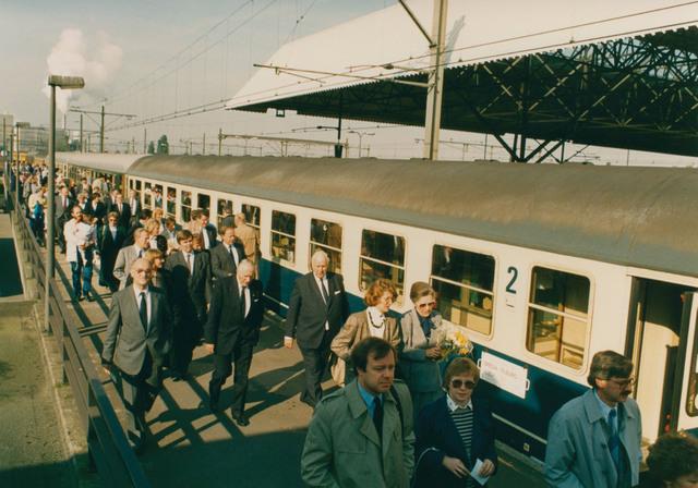 651284 - Tilburg, 125 jaar stad aan het spoor. Manifestatie. Op het postperron van station Breda stond een stoomtrein met zes wagons klaar om de gasten via Gilze-Rijen naar Tilburg te vervoeren. Naast mevrouw Van Harten (met bloemen) loopt Minister Neelie Smit-Kroes. In totaal zijn er 150 gasten voor deze heugelijke dag uitgenodigd.