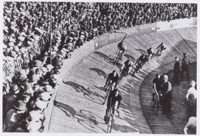 """054427 - Sport. Wielrennen. op de Tilburgse wielerbaan vond onder geweldige belangstelling een wielerwedstrijd plaats, waar de """"groten"""" aan deel namen; tijdens de koppelwedstrijden vooraan Jan Pijnenburg en Wals;"""