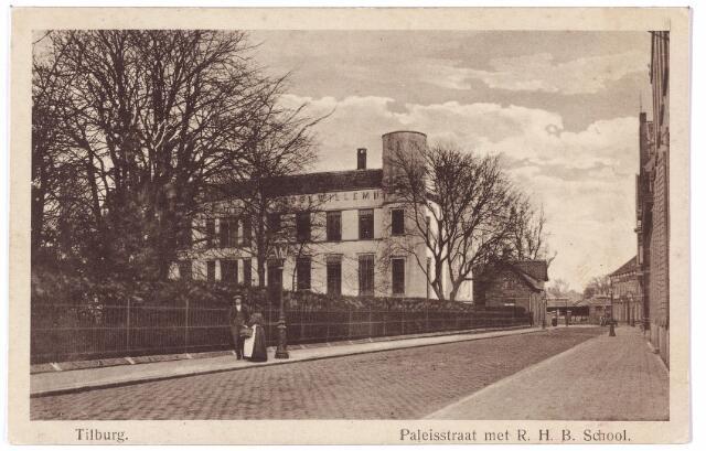 002402 - Onderwijs. De voormalige Paleisstraat, nu Stadhuisplein met links de voormalige Rijks H.B.S. Koning Willem II.  Aan het einde van de omheining de bijgebouwen van de rijks H.B.S. Deze werden gesloopt de jaren 1935/36 toen het gebouw werd verbouwd tot paleis-raadhuis.