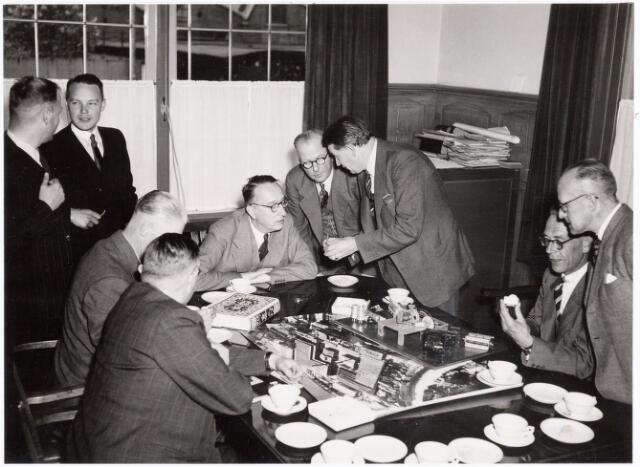 038672 - Volt. Zuid. Bezoek van B&W van Tilburg aan Volt op 26-4 1949. Belangstellend bekijkt men hier de producten die Volt toen maakte. Links staande Ir. Vroom hoofd bedrijfsbureau en Mr.Ledeboer directiesecretaris Volt. Links vooraan zittend de wethouders Janssens en H.F. van Dullemen, verder v.l.n.r. Baron van Voorst tot Voorst burgemeester, wethouder Appels, Ir. Kipperman directeur Volt, Dhr.de Vleeschouwer bedr.leider Volt en wethouder Hoogers.  Op de tafel ligt het boek 50 jaar met een kroon boven de titel. Zeer waarschijnlijk heeft dat te maken met het feit dat kort daarvoor (september 1948) Koningin Wilhelmina na 50 jaar de kroon overdroeg aan Koningin Juliana. Uit sommige bronnen blijkt dat Ir.Kipperman nogal veel op had met het Oranjehuis Nieuwe Goirleseweg werd dat jaar Voltstraat.