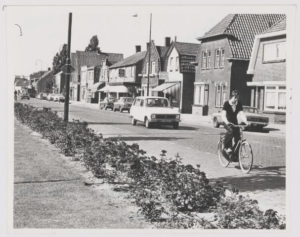 082334 - Een leuke impressie van een drukke verbindingsstraat tussen oude Rijksweg en het centrum van het dorp. Een straat met diverse buurtwinkels.