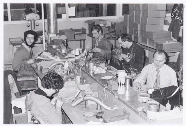 """039341 - Volt. Noord. Hulp-afdelingen, Sociale Zaken, Zorg. Volt heeft altijd veel werk uitbesteed aan de sociale werkplaatsen. Aanvankelijk het Martha-atelier later de Riethoorn en tegenwoordig de Diamant Groep geheten. Op de foto werknemers van de """"Riethoorn"""" in actie voor Volt omstreeks 1975."""