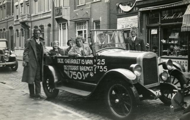"""653877 - Chevrolet  model 1925. Rechts het pand van bakker Marijnen. De woorden """"Ze zijn er"""" zijn nog steeds te zien op de voorgevel."""