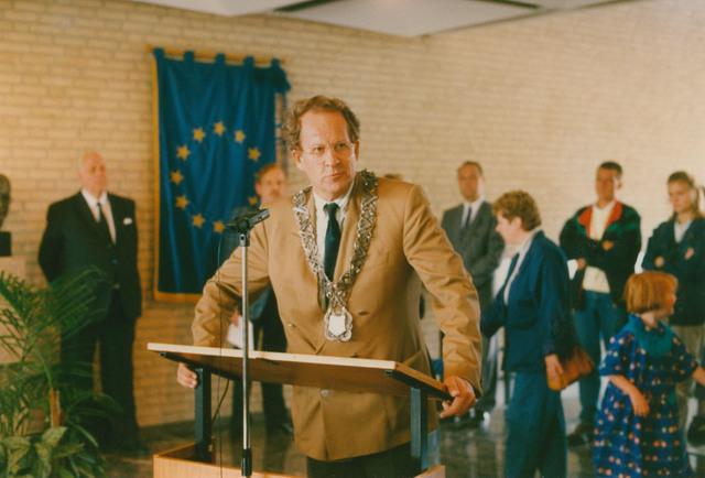 651321 - Tilburg, 125 jaar stad aan het spoor. Manifestatie. Burgemeester Gerrit Brokx van Tilburg (16 mei 1988 - 1 juni 1997 - CDA) sprak vervolgengs zijn welkomstwoord uit.  Op de achtergrond de vlag van de Europese Unie met de toen nog 12 sterren ( van de 12 lidstaten).