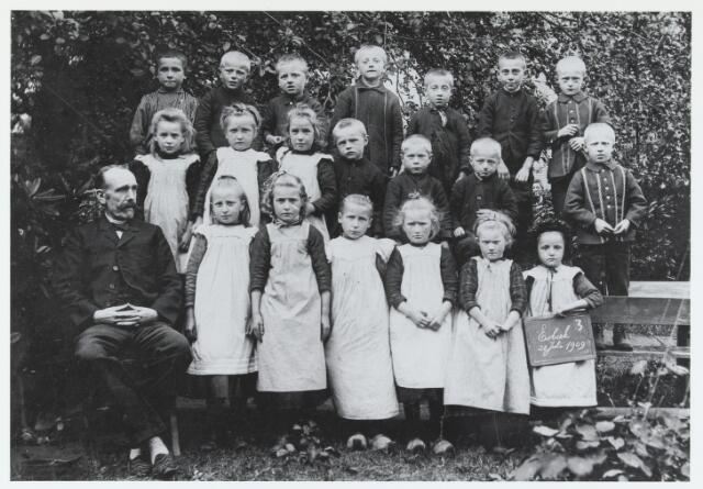 055920 - Basisonderwijs.  Klassenfoto openbare lagere school in 1909 te Esbeek. Eerste rij v.l.n.r. meester De Bruin, Mieke de Kort, N.N., Mieke Lambregts, Jans Schellekens, N.N. en Cato Brouwers; Tweede rij v.l.n.r. Cato van Dommelen, De Kort, Ant Lambregts, Janus Smolders, Piet Lambregts, Jan Lambregts en Jan Hesselmans; Laatste rij v.l.n.r. N.N., N.N., Toon Wilborts, Van Dommelen, Piet de Kort, Koob de Kort en Janus Hesselmans.
