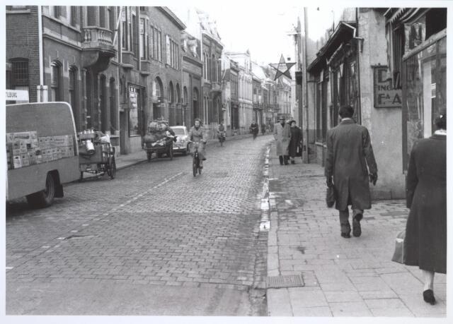 """026953 - Nieuwlandstraat in 1957 gezien vanuit de vroegere Zomerstraat (thans Heuvelstraat). Rechts bij de poort rijwielhandel Heijne, schoenmakerij Spitters en bakkerij """"In de Oude Ster"""", genoemd naar een eerder in deze straat bestaande gelijknamige bakkerij die in 1914 was gesloopt.  Links, met bordes, een herenhuis uit het begin van de 20ste eeuw en daarnaast slagerij Verhagen, voorheen Ooms. Dit winkelpand, met authentiek interieur, werd in 1922 gebouwd. Vervolgens de in 1965 afgebrande ijzer- en staalhandel van Piet Mercx"""