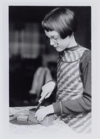 050037 - Meisje snijdt peperkoek. Foto uit ´Je Taalboek´ van frater Victor van Nispen.