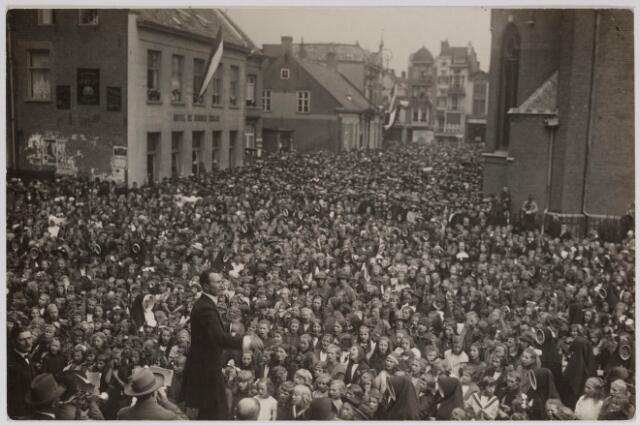 042637 - Een enorme mensenzee op de Oude Markt in september 1923 tijdens een muzikale hulde bij het stadhuis ter gelegenheid van het regeringsjubileum van koningin Wilhelmina. Hier een groep schoolkinderen die onder leiding van de heer Groot, dirigent van de NK Harmonie, een lied ten gehore brengt