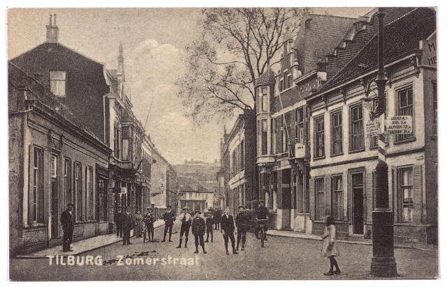 001207 - Zomerstraat  bij de splitsing Zomerstraat/Bredaseweg. De wegwijzer rechts wijst het verkeer via de Zomerstraat en de Korvelseweg richting Goirle, Riel, Alphen en Turnhout. Geheel links de ingang van de Schoolstraat. De straatwand rechts en links is in de jaren zestig afgebroken voor de aanleg van de Schouwburgring. Op de plaats van de huizen links is nu een parkeerterrein. Op de achtergrond de kruising met de Nieuwlandstraat. Rechts het pand van de familie Boelaars, Zomerstraat nr. 42, links hiervan Zomerstraat 40. Dit pand werd rond 1910 gebouwd voor notaris Van Eijl, die tot 1911 aan de overkant op nr. 27 woonde. Van Eijl werd geboren te Tilburg op 15 juli 1854 en overleed aldaar op 1 januari 1933. Hij was getrouwd met Henriëtte M.A.D. Mathijsen. Tijdens de Tweede wereldoorlog zat in dit pand de Nederlandse Volksdienst, het bureau Winterhulp Nederland en de Luchtbeschermingsdienst. Na de oorlog werd het pand in gebruik genomen de geallieerde krijgskrachten.