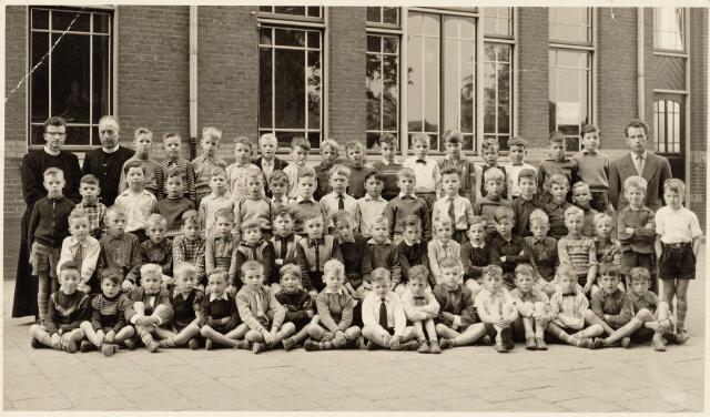 051198 - Basisonderwijs. Klassenfoto r.k. lagere school. Heilig-Hart school. Deze school was toen nog een jongensschool en behoorde onder de parochie Noordhoek. Deze foto is gemaakt ter gelegenheid van de eerste H. Communie aangeboden door het oudercomité van de school. Deze foto is genomen op de speelplaats van de school en men ziet 2 klassen van elk 34 leerlingen in het eerste leerjaar. Schooljaar 1956-1957 in de leeftijd van 6 à 7 jaar eenieder op de foto. De groep staat op de speelplaats ter linkerzijde van het gebouw voor de zesde klas. Afgebeelde personen zijn links frater Petrus  (onderwijzer 1e klas) en frater Christiaan ( onderwijzer 6e klas en hoofd der school). Beide fraters behoren tot de orde van de fraters van Tilburg aan de gasthuisring. Rechts ziet men onderwijzer Leyten (onderwijzer van de andere 1e klas).   Enkele namen van kinderen zijn bekend. Eerste rij van boven v.l.nr. 1. Frans Adriaansen. 3. Frans de groot. 4. Peter Ligtvoet. 7.Johan Mutsaerts. 14. Ad v.d. Oetelaar. Tweede rij van boven v.l.n.r. 3. Paul v.d. Akker. 5. Christo Vesters. 6. Jo van Roessel. 9. Arie van Kleef. 10. Hans Ophuis. 16. Jac Janssen. Derde rij van boven v.l.n.r. 2.3 Tweeling Hengeveld. 12. Jan Paulissen. 14. Sjors Zieltjens. 15. Joop Kouwenberg. 16. Kees v. Dun. 17. Hennie Loots. Onderste rij v.l.n.r. 1. Michel Maas. 3. Peter Hettema. 5. Raymond v.d. Weegen. 6. Groenen 9. Peter Koenen 11. Musters.