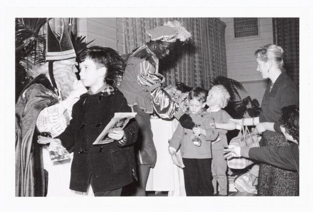 038847 - Volt.Zuid. Ontspanning. Sint Nicolaasfeest in 1960. Bij het afscheid deelt Piet nog een zakje snoepgoed uit. Sinterklaas. St. Nicolaas