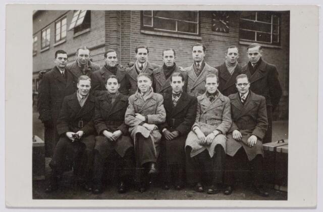 044364 - WOII; WO2; Textiel. Arbeitseinsatz. Groepje werknemers van H. F. C. Enneking op de binnenplaats van de fabriek aan de Goirkestraat in het najaar van 1943. De groep staat gereeed om in het kader van de Arbeitseinsatz te gaan werken in Duitsland. Enneking toonde zich een goede werkgever door voor allen een koffer (rechtsonder) te laten maken door de fabriekstimmerman. Het was 75 centimeter lang, 23 centimeter hoog en 40 centimeter breed en was gevuld met levensmiddelen, zeep en dergelijken. Op de foto vooraan, derde van links Jaoneke Kuijpers en rechts naast hem Wil van Arkel. Op de achterste rij, vierde van rechts Toon Jansen. Hij keerde als enige niet terug uit Duitsland: op 22 juni 1943 kwam hij om het leven tijdens een bombardement op Krefeld