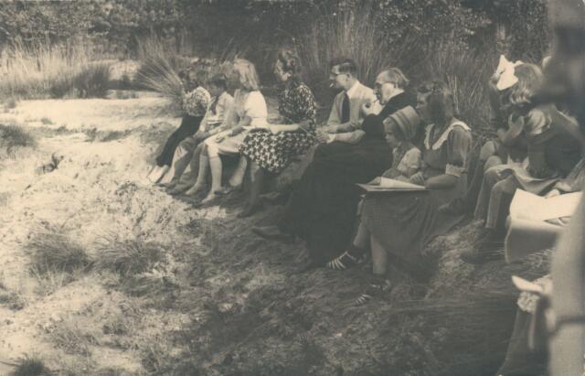 650760 - Brabants Studenten Gilde. Onze Lieve Vrouw van de Goede Duik, Tilburg. Een groep mensen (waarschijnlijk tijdens 'Kinderjool', een kinderfeest) op het landgoed Merle van de familie Van Nunen. In het midden (met pijp) de geestelijke Frans Siemer.