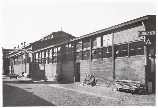 038634 - Volt. Zuid. Gebouwen. Ca. 1960. De gebouwen G en H uit 1928. Het gebouw G (met fiets) was een kantoor en werd bemand door het Productie-bureau, later onderdeel van Materials Management. Het achterste gebouw H deed tot 1961 dienst als kolengestookt ketelhuis. Daarna, tot de verhuizing naar noord, was hier de alkydafdeling gevestigd. (Een soort kunststofspuiterij). De foto is genomen in de richting  Z-ZW.
