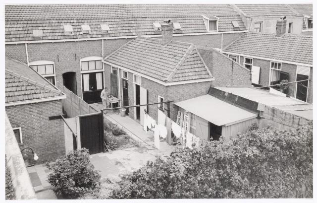 """038639 - Volt. Zuid. Gebouwen. ± 1960. Een kijkje vanaf het oude hoofdkantoor gebouw J op de dienstwoning van """"hoofdportier"""" of hoofd bewaking Schoppert aan de Voltstraat.Bijde woningen waren eigendom van Volt. Dhr. Resler van de timmerwinkel is waarschijnlijk met een reparatie bezig. De linkse woning was in gebruik door de personeels-winkel. De achtertuin hiervan is in gebruik genomen door de buurman de Hr. Schoppert."""