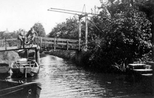 064905 - Drimmelen. De Vaart/Herengracht. Brug. De roeiboot op de voorgrind noemde men een Sintel. Onder de brug links ligt nog een houten sintel. Op de brug staat de tweeling Jacob en Hendrik Schrier. Dit bruggetje lag aan het z.g. Fort. Geschreven als Fort en als Ford zoals op onderschriften bij verschillende foto\'s blijkt. U kijkt in de richting van de sluis. Links onder de brug een tjalk. Achteraan rechts is nog juist zichtbaar de splitsing naar de Put. Op die hoek was de scheepswerf van Niek van den Hoven. Rechts vooraan een aanlegplaats voor scheepsreparatie bij Adriaan van Suylekom