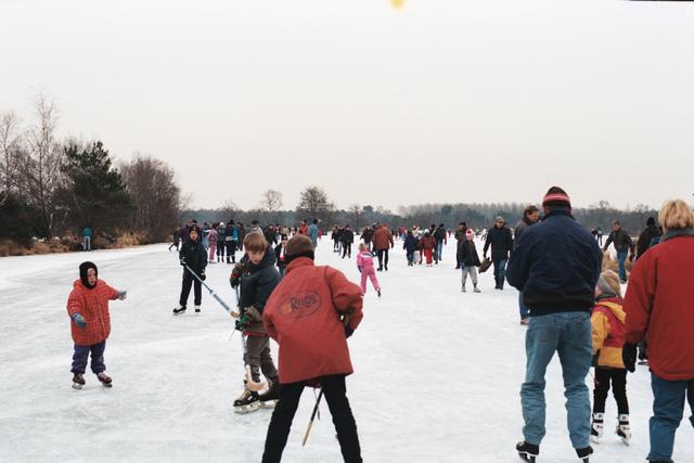 1237_010_756_030 - Winter. Schaatsen. IJspret bij natuurijsbaan de Flaes in de bossen van landgoed De Utrecht bij Esbeek. Mensen vermaken zich op het bevroren ven.
