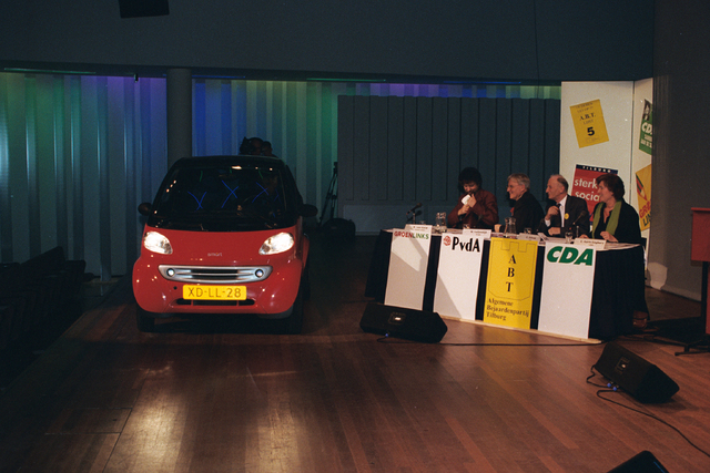 1237_002_221-1_004 - Politiek. Een vergadering voor de gemeenteraadsverkiezingen in de Tilburgse concertzaal in 1999. Zittend rechts: R. van Gurp (GroenLinks), W. Luijendijk (PvdA), G. Schriek (A.B.T.) en Els Aarts Engbers (CDA). De Smart op het podium is dankzij de belettering aan de zijkant een promotiemiddel om inwoners van Tilburg te laten stemmen op 3 maart.