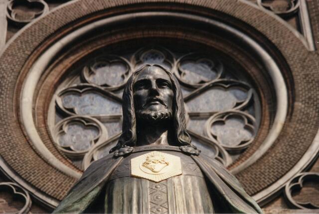 602042 - H. Hartbeeld aan de Heuvel. Op de achtergrond het roosvenster van de St. Josephkerk.
