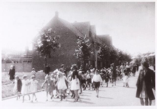 013633 - Tweede Wereldoorlog. Om geld in te zamelen voor de aankoop van materialen voor de vrijwillige luchtbescherming werden diverse activiteiten georganiseerd. Hier, in de Groenstraat midden juli 1944, lopen kinderen achter een geluidswagen die hen oproept deel te nemen aan kinderspelen op een terrein aan de Ringbaan-Zuid.