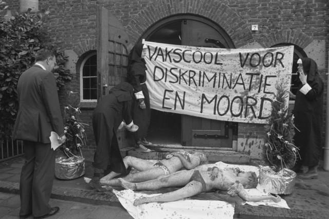 """TLB023002685_001 - Demonstratie. Actievoerders verkleed als nonnen en twee """"vermoorde"""" vrouwen voor de ingang van ?   Spandoek """"Vakscool voor diskriminatie en moord"""""""