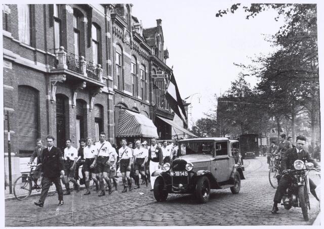 020925 - Een wandelclub paradeert op de Heuvel omstreeks 1934. Op de achtergrond de tram