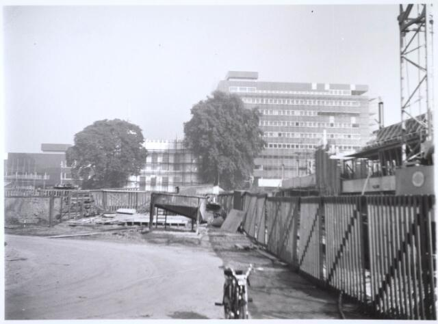 024282 - Bouwput voor de bibliotheek, Kultureel Sentrum en flats aan het Koningsplein. Op de achtergrond het nieuwe stadskantoor