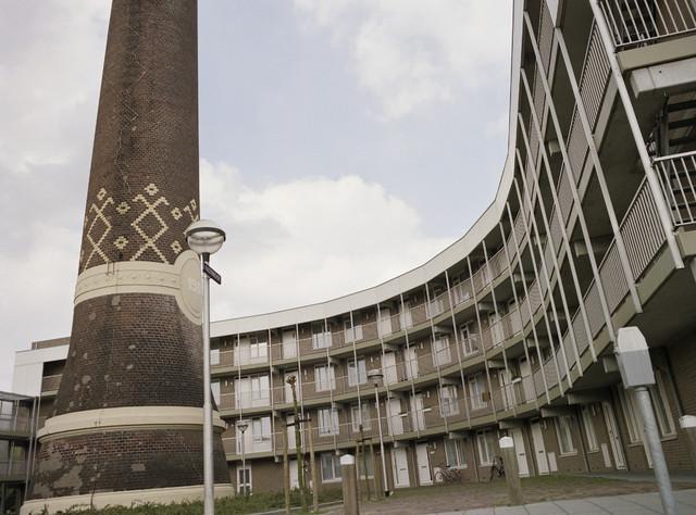 """TLB023000153_004 - Schoorsteen BeKa met appartementen Kazernehof. In 1853 richtte Pieter van den Bergh en zijn vrouw Rijka Krabbendam de Wollenstoffenfabriek Van den Bergh Krabbendam op, later afgekort tot BeKa. In 1859 vestigde hij zijn bedrijf in een deel van de voormalige Lancierskazerne aan de Oisterwijksebaan (thans Sint Josephstraat). In de loop der tijd werd het bedrijfscomplex aanzienlijk uitgebreid en was het qua omvang een van de grootste textielfabrieken in Tilburg. In de jaren zestig kwam ook hier de buitenlandse concurrentie hard aan en in 1968 werd de productie van wollen stoffen stopgezet. Er werkten toen nog 278 personen. De bedrijfspanden die bij de kazerne waren bijgebouwd werden gesloopt. Alleen de schoorsteen uit 1904 bleef overeind. Deze markeerde vroeger een monumentaal ketelhuis. In de oorspronkelijke en later gerestaureerde gebouwen kwamen kantoorruimtes en in 1988 onder meer het gemeentearchief Tilburg (vanaf 2007 Regionaal Archief Tilburg). Op delen van het voormalige fabrieksterrein werden woningen en appartementen gerealiseerd. Foto genomen in kader """"SPB / BouwRai"""" ter promotie van het """"Samenwerkingsverband Praktijkopleiding Bouw"""" en de tweejaarlijkse bouwmaterialenbeurs in de Amsterdamse RAI."""