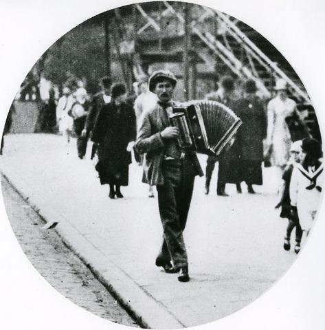 065961 - Muziekleven. Straatmuzikant. Accordeonist. Vanuit de Koestraat vermaakt deze straatmuzikant de kermisgangers met zijn accordeon muziek. Op de achtergrond is de voetgangersbrug te zien