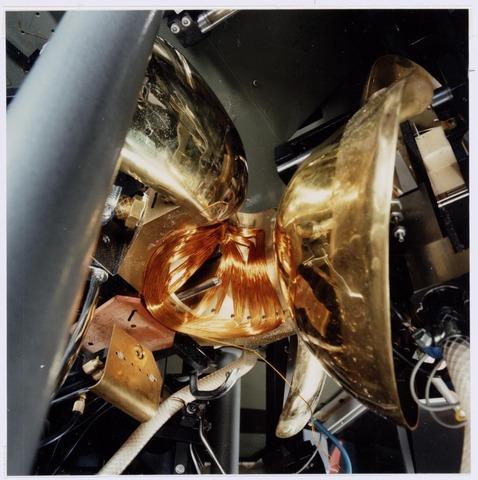 """038977 - Volt. Noord.Productie of fabricage afd. Deflectie Units. Een deflectie unit is een ingewikkelde electro magneet die er voor zorgt dat een beeld op een televisie scherm wordt uitgeschreven. De benodigde spoelen daarvoor werden gewikkeld in zeer geavanceerde mallen. Hier zien we een mallenset op een machine in geopende toestand of de zogenaamde """"losstand"""". De gewikkelde spoel is duidelijk zichtbaar en wordt onmiddellijk na het openen van de mal uitgestoten of gelost. Deze machines waren in staat elke 16 seconden een beeld-of lijnspoel af te leveren en wel volautomatisch."""