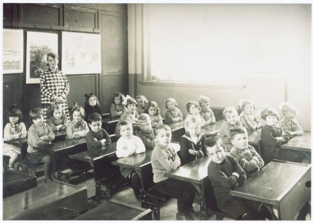 062043 - Basisonderwijs. Klassenfoto. Bewaarschool / Kleuterklas Enschot  onder leiding van juffrouw Marie Denissen; zittend in de voorste rij banken v.l.n.r. Pietje Mol, Frieda Verhoeven, Riet van Esch, Treesje Segers, Schoonings, Jan Schilders, Wil Hoogendoorn, Jo Schellekens, Van Os, Harry van Baast en Jo Schoonings; op de achterste rij banken v.l.n.r. Fien de Jong, de Kroon, Annie van Nieuwburg, Cor v.d. Wiel, Anneke de Jong, Mien Denissen, Fien van Baast, Mien Bambacht, Anneke v.d. Wouw, Riet Denissen, Sien de Bakker en Jeanne Vugts