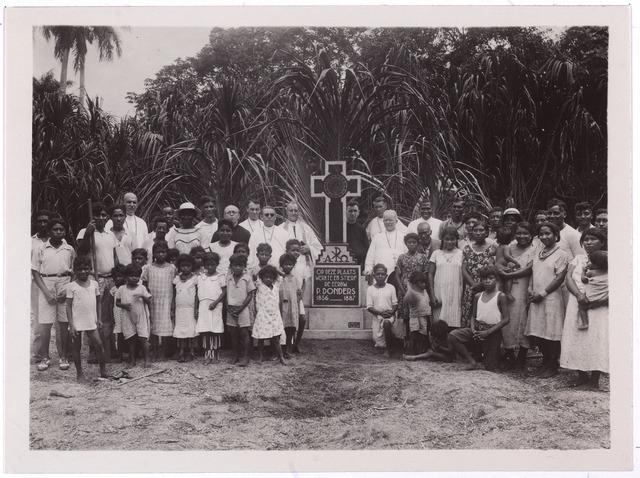 004086 - In 1938 werd het houten kruis dat sinds 1933 op het eerste graf van de zalige Peerke Donders stond, vervangen door een wat groter stenen kruis. Hiervoor had frater Cornelis Smits, links naast dame met hoed, in Nederland geld ingezameld. Het kruis stond op de plantage Batavia in het Surinaamse district Coppename. Het tijdelijke graf is later overgeplaatst naar de kathedraal van Paramaribo.