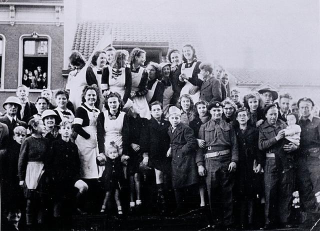 1696103 - Rode Kruis afdeling Tilburg. Rode Kruis hulpverleners bij het bevrijdingsfeest op 4 november 1944 in de Paleisstraat. Zij werkten onder andere in de AaBe-fabriek waar een opvangcentrum was ingericht voor de vluchtelingen uit het nog niet bevrijde Noord-Nederland. Op de tank, links naast de Schotse militair en met hel Mies Fouchier. Op de eerste rij, rechts naast de man met de helm, Cor Weijters en nast haar mejuffrouw Fouchier. WOII. Tweede wereldoorlog. Bevrijding.
