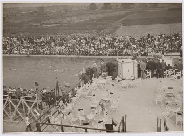 """043924 - Zwemwedstrijd in het gemeentelijk zwembad aan de Ringbaan-Oost op de dag van de opening, 1 augustus 1931. Op de voorgrond het terras boven de machinekamer, in de krant geprezen om """"het prachtige uitzicht vanaf dit punt op gepavoiseerde zwembasins""""."""