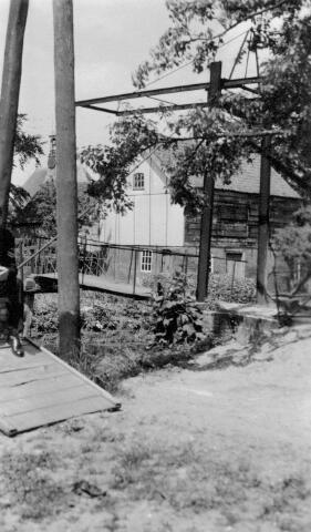064893 - De Herengracht met brug. Aan de brug kan men zien, dat deze foto van latere datum is dan ca 1926. De houten leuningen van de brug zijn inmiddels vervangen door een ijzeren leuning. Het gebouw op de achtergrond is een leerlooierij die in latere jaren is afgebroken, waarschijnlijk van A.A. van der Sluys. Je kunt nu nog steeds zien waar deze leerlooierij heeft gestaan, omdat daar de ruimte tussen de straat en het water breder is.  Deze leerlooierij stond aan de zelfde kant als de Nedederlands Hervormde Kerk, welke op de achtergrond nog zichtbaar is.  Gegevens over de vlonder links met daarop nog gedeeltelijk iemand in soldaten uniform ontbreken.  Naar rechts gaat men richting van de sluis.