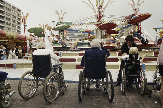TLB023000074_001 - Bezoekers in rolstoel voor kermisattractie tijdens gehandicaptenmiddag.  De Tilburgse Kermis is de grootste kermis in de Benelux. Er staan jaarlijks tussen de 230 en 240 attracties uit binnen- en buitenland, in een 4,5 kilometer lang lint door het centrum van de stad. De kermis trekt jaarlijks meer dan een miljoen bezoekers en is daarmee een van de best bezochte evenementen van Nederland.