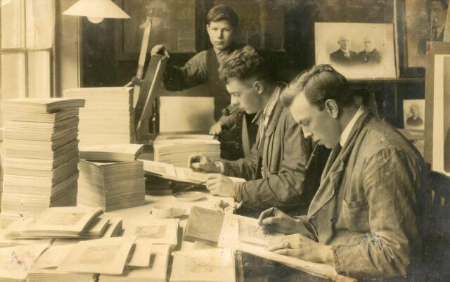 602006 - Interieur van het atelier van hoffotograaf Van Beurden aan de Willem II-straat 39. De twee leerling fotografen zijn foto´s of reproducties aan het retoucheren. Daarachter staan een jongen aan de drukpers. Gezien de grote hoeveelheid foto´s of prenten die links op de foto staan opgestapeld had het atelier opdrachten genoeg. Rechts staan de geretoucheerde portretfoto´s te drogen. De persoon in het midden is Leo van Beurden (1905-1961), de latere en laatste fotograaf van atelier A. van Beurden.