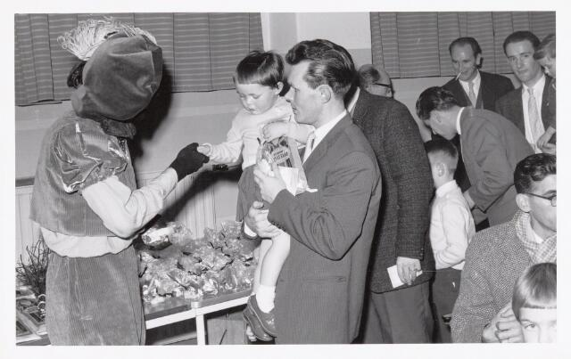 038712 - Volt. Oosterhout. Sint Nicolaasviering voor de kinderen van het personeel in 1960. In het midden Dhr. Hermans, destijds baas in de gereedschapmakerij, wiens dochtertje zwarte piet een hand geeft. Fabricage- of productie vond in Oosterhout plaats van april 1951 t/m 1967. Sinterklaas. St. Nicolaas