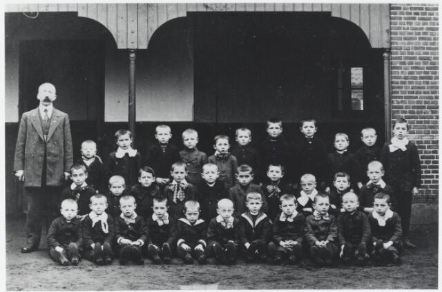 055567 - Onderwijs. Klassenfoto. Meester Tooten op de speelplaats van de openbare lagere school aan de Paardenstraat met zijn leerlingen.  Plannen om een nieuwe openbare lagere school aan de Doelenstraat te bouwen, vonden in 1921 geen doorgang, waarnaar door het kerkbestuur aan de Varkensmarkt een katholieke bijzondere lagere school voor jongens gebouwd werd. Deze Petrus Canisiusschool werd op 22 december 1925 geopend. Ondanks protest van de protestanten, werd in dat jaar door raad besloten om de openbare school aan de Paardenstraat te sluiten. dit besluit werd echter door Gedeputeerde Staten teniet gedaan.