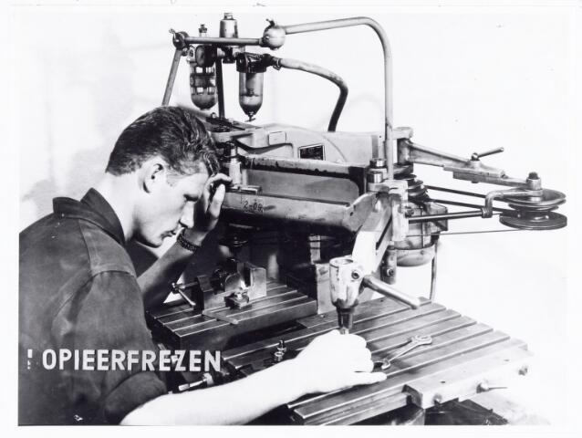 038572 - Volt. Noord. Opleidingen. Foto gebruikt bij de tentoonstelling 25 jaar vakliedenopleiding Volt in 1964. Hier een oefening kopieerfrezen. Soms werd de machine gebruikt om teksten en of cijfers in gereedschappen te frezen. Men kon ook nauwkeurig profielen overnemen van bestaande uitsparingen.
